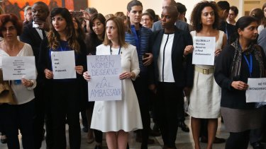 United Nations staff, some holding signs, stand in a silent protest against a UN meeting to designate Wonder Woman as an honorary ambassador.