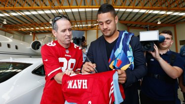 Man of many codes: Jarryd Hayne signs autographs for fans during a press conference at Gold Coast Airport on Wednesday.