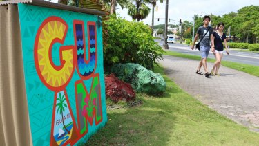 Tourists walk through a shopping district in Tamuning, Guam - the nearest US territory to North Korea.
