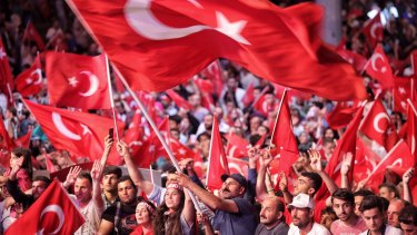 Supporters of Turkish President Tayyip Erdogan wave Turkish flags as they gather in Istanbul's central Taksim Square on July in the aftermath of Friday's failed military coup attempt.