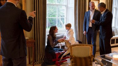 Prince George plays on the rocking horse previously given by the Obamas.