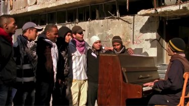 Ayham al-Ahmed rehearsing a song on a rooftop in Yarmouk refugee camp in a scene from the film <i>Blue</i>.