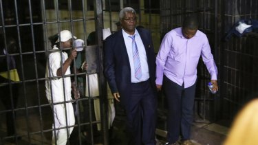 Zimbabwe's former finance minister, Ignatius Chombo, centre and Kudzanai Chipanga are led to a prison truck at the magistrates courts in Harare.