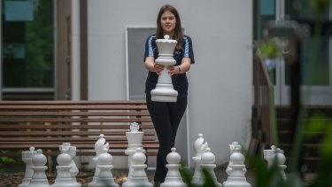 One of ACT's top girl chess players, Saffron Archer, holds the white queen.