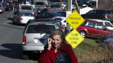 A woman mourns while speaking on the phone near Sandy Hook Elementary School, after the December 2012 shooting there which left 20 children and six school staff dead.