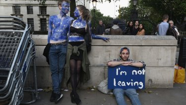 A young couple painted as EU flags protest on outside Downing Street against the United Kingdom's decision to leave the EU.