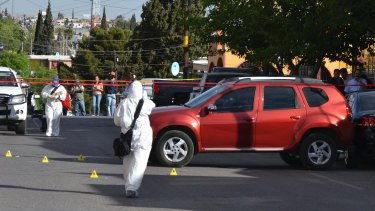 Forensic workers on the scene where journalist Miroslava Breach was shot and killed outside her home in Chihuahua, Mexico.