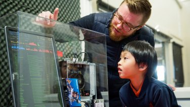 Eight-year-old Wooranna Park Primary School student Seth Yee and teacher Kieran Nolan with a server that authenticates Blockchain data.