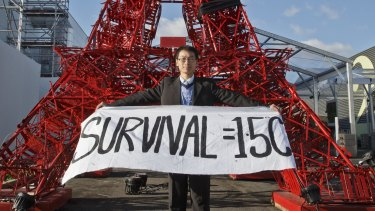 A representative of a NGO displays a banner supporting a target to keep global warming below 1.5 degrees in front of a reproduction of the Eiffel tower at the Paris climate summit.