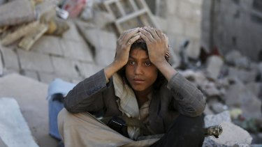 A member of the Houthi group sits on the rubble of houses destroyed by an overnight Saudi-led air strike on a residential area in Yemen's capital, Sanaa.