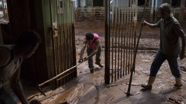 People remove mud from a damaged home in Barra Longa after a dam burst.