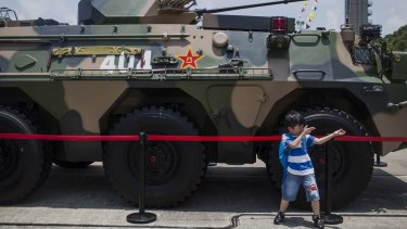 Aspirations of a nation: a child pretends to hold a gun while posing for a photograph in front of a People's Liberation Army tank.