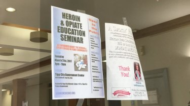 A flyer for a heroin and opiate education seminar hangs along side other community news at the front door of the Tipp City, Ohio municipal offices.