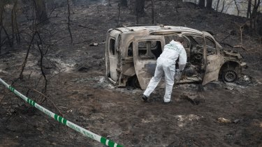 A police scientist inspects the remains of the car where two women died after a wildfire in Pontevedra, Spain.