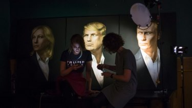Two women wait in front of portraits of Marine Le Pen, Donald Trump and  Vladimir Putin for a live telecast of election results in a pub in Moscow.