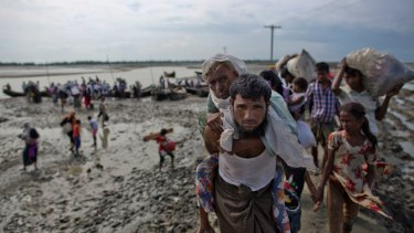 A Rohingya Muslim man from Myanmar carries an elderly woman after they crossed the border into Bangladesh.