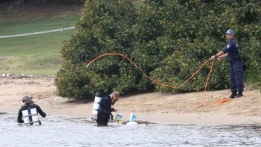Police divers search the water around Cabarita Wharf, where the body of a woman was found.