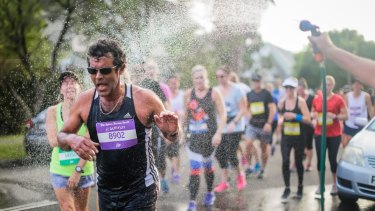 Runners get water relief at The Sydney Morning Herald Sun Run on Saturday.