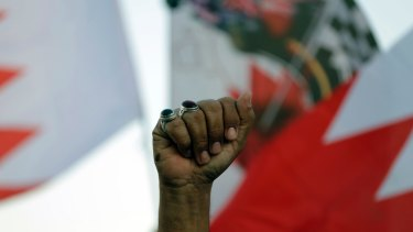 A Bahraini anti-government protester raises his fist amid national flags during a rally against the Formula 1 Bahrain Grand Prix in April.