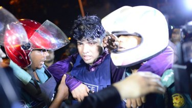 An injured Bangladeshi policeman being assisted after the attack.