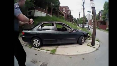 University of Cincinnati police officer Ray Tensing approaches a car with his gun drawn.