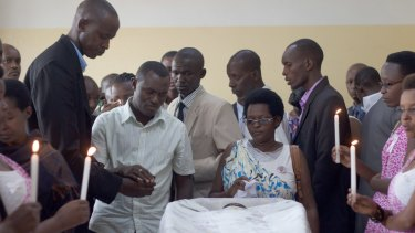 Friends and relatives gather around Egide Niyongere's coffin for a final goodbye.