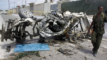 A Somali soldier stands near the wreckage of a car bomb outside the UN's office in Mogadishu, Somalia, on July 26, 2016.
