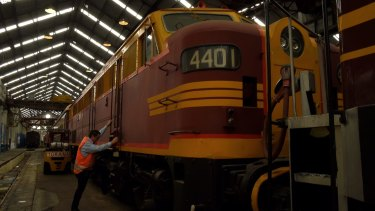 The Large Erecting Shop manager Alan Gardner climbs aboard a carriage at Eveleigh Railway Precinct, Eveleigh.