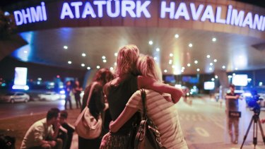 Passengers embrace each other at the entrance to Istanbul's Ataturk airport.