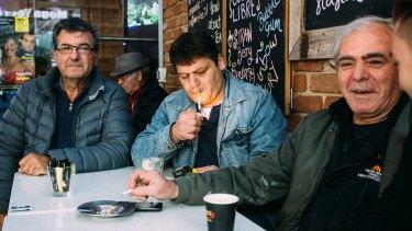 Niko Penesis (from left), Kostas Dotas and Spiros Psiroyiannis enjoy a morning smoke and coffee at Kentro in Eaton Mall.