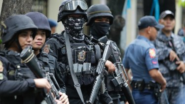 Armed police keep watch as men suspected of being Marawi militants arrive at the Department of Justice in Manila, Philippines.