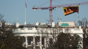 "Greenpeace protesters unfurl a banner that reads ""Resist"" at a site near the White House."