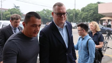 Jeff Sikima, centre, the husband of Jenny Jiang, who had arranged visas for Crown clients and was one of only three defendants on bail.