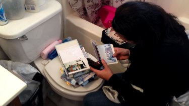 A woman straddles the toilet and rifles through photo albums.