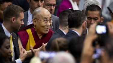 The Dalai Lama greets the crowd as he leaves after delivering his speech - A Peaceful Mind in a Modern World - at American University's Bender Arena in Washington.