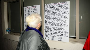 Cessnock Councillor Catherine Parsons looks at two protest placards left outside the council meeting.