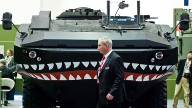 A businessman walks past an Iveco vehicle during the 2013 edition of the Defence & Security Equipment International arms fair  in London.