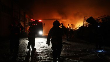 Israeli firefighters extinguish a burning factory hit by a rocket fired from the Gaza Strip on June 28, 2014 at an industrial zone in the southern city of Sderot.