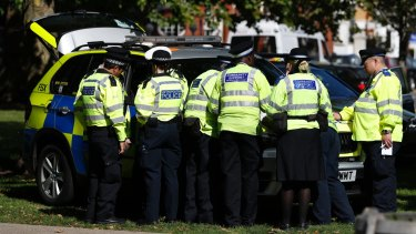 Police and community support officers gather round a police vehicle near where the incident happened.