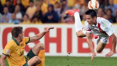 Australia's Alex Wilkinson clashes with China's Wu Lei.