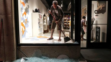 Scott McRoberts helps clean up broken glass after a violent crowd broke windows in University City, Missouri.