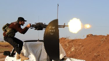 A Member of Syrian opposition group fires during clashes with IS militants in Aleppo, Syria.