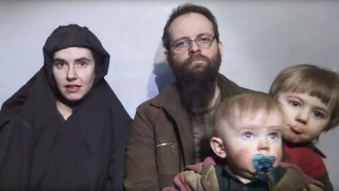 Caitlan Coleman talks in an undated Taliban video while her Canadian husband Joshua Boyle holds two of their children .