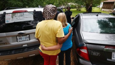 Neighbours console each other near a house where several people were killed on Saturday night in Lincoln County, Mississippi.