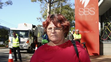 Mt Druitt resident and Struggle Street subject Peta Kennedy stands outside SBS as rubbish trucks blockade the broadcaster in protest.