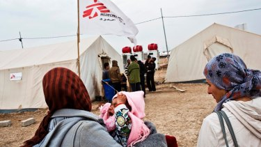 A mother carries her baby to the MSF medical clinic in Domiz refugee camp, Kurdistan, Iraq. Photographed in 2013.