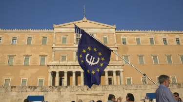 A protester holds a European Union flag with a euro currency symbol  at a rally outside the Greek parliament.