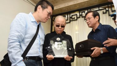 Liu Xia, centre, holds a portrait of her husband Liu Xiaobo during his funeral in Shenyang, north-eastern China, on Saturday.