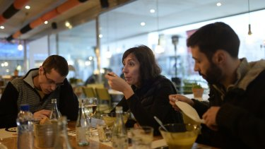 Time out: Simona Levi, 48, from Italy, centre, Sergio Salgado, 35, left, and Alfa Sanchez, eat in a restaurant during from a session working with Xnet in Barcelona.
