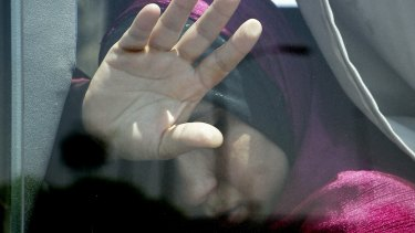 A relative of a passenger on the EgyptAir flight puts her hand on the window from inside a bus at Cairo airport.